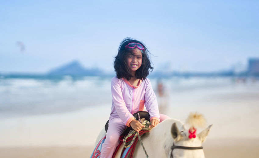 Girl riding on howoman wearing mask on beach against sky