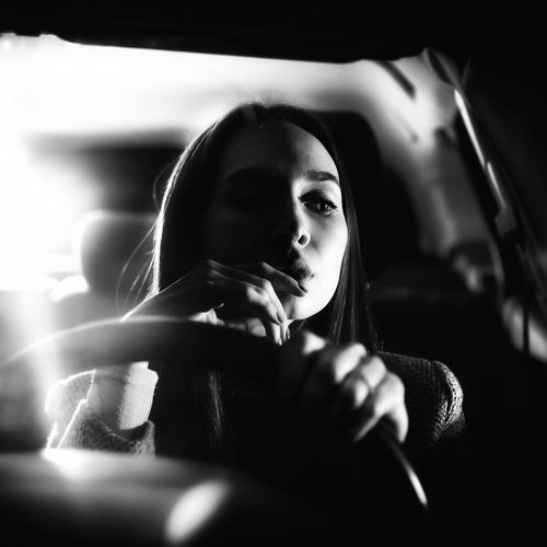 Beautiful woman sitting in car at night