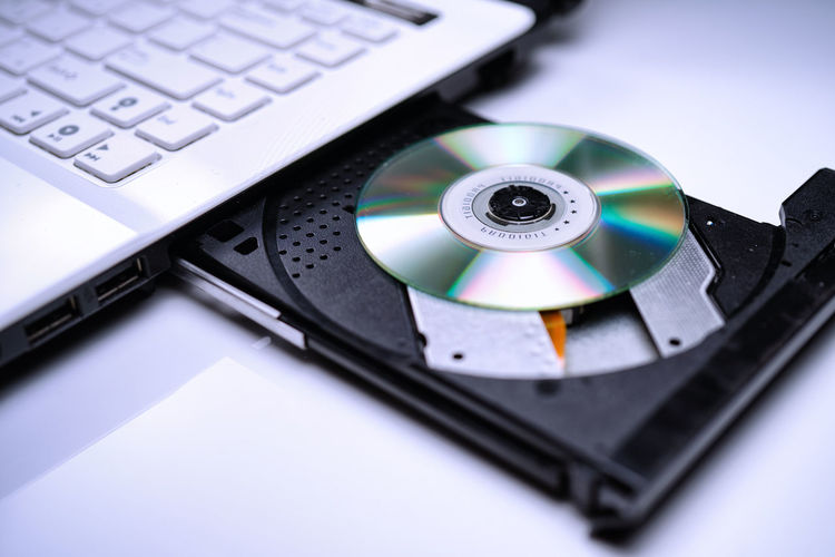 DVD Disk on the white Laptop DVD ROM Tray. A Piracy conceptual image of burning data into DVD Disk Burning DVD Isolated Movies Music Pirate Tray Archieve Computer Data Device Digital Art Disk Dvdr Dvdrom Hackers Keyboard Laptop Laser Multimedia Notebook Optical Piracy Software Storage