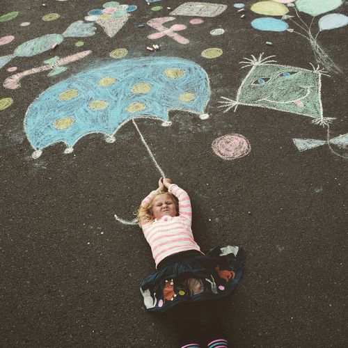 High angle view of girl lying by drawing on road