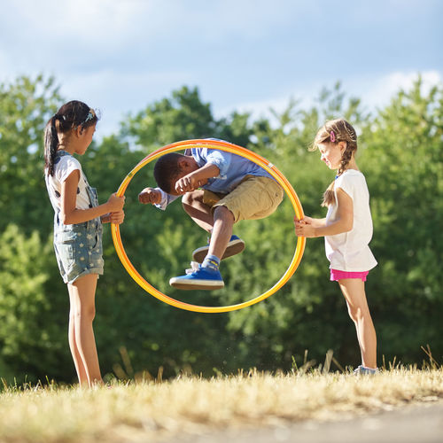 Boy jumping through plastic hoop held by female friends at park