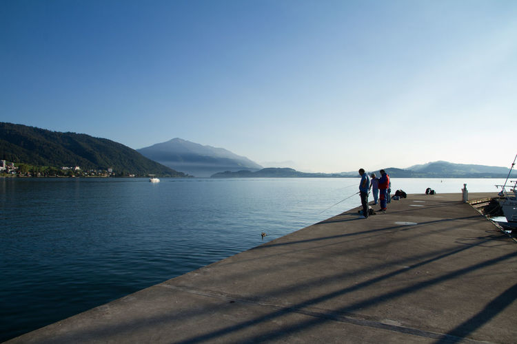 People fishing at lakeshore against clear sky
