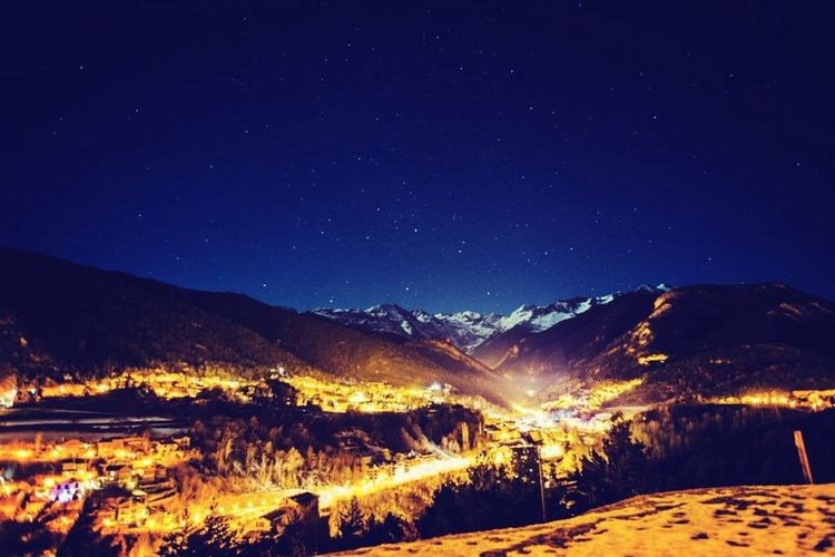 Aerial View Of Illuminated Town On Mountains Against Clear Blue Sky At Night