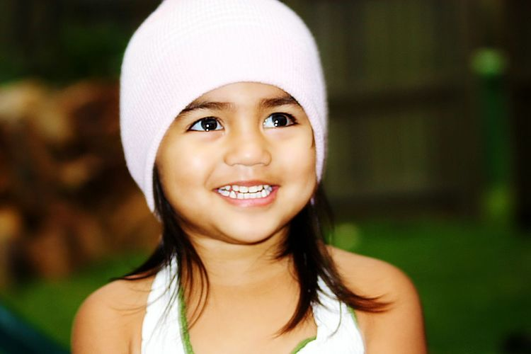 Close-up of happy girl wearing knit hat looking up