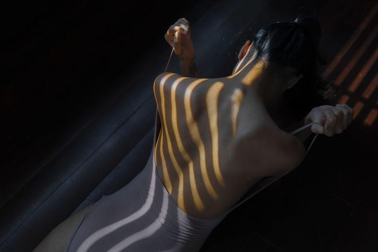 Rear view of woman pulling swimwear strap while lying on sofa