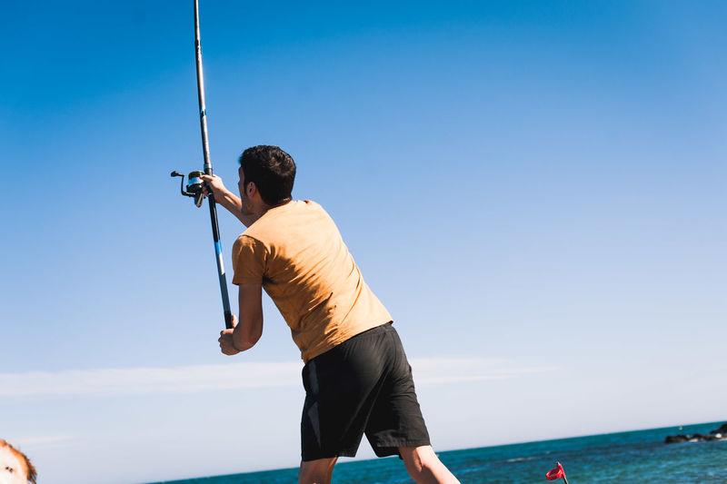 Rear view of man standing by sea against clear sky