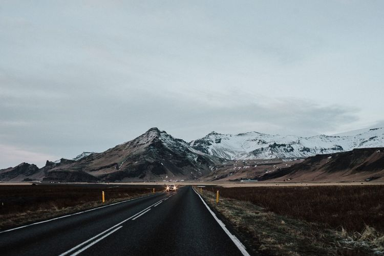 Road by mountain against sky