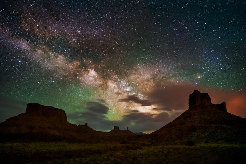 View of mountain against night sky filled with stars and airglow