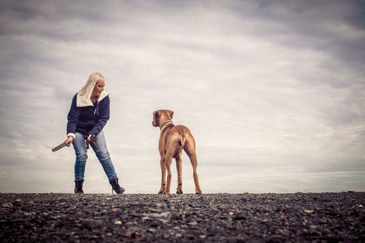 Animal Themes Blond Hair Casual Clothing Day Dog Domestic Animals Friendship Full Length Mammal Nature One Animal One Person Outdoors People Pets Real People Sky Standing Young Adult Young Women