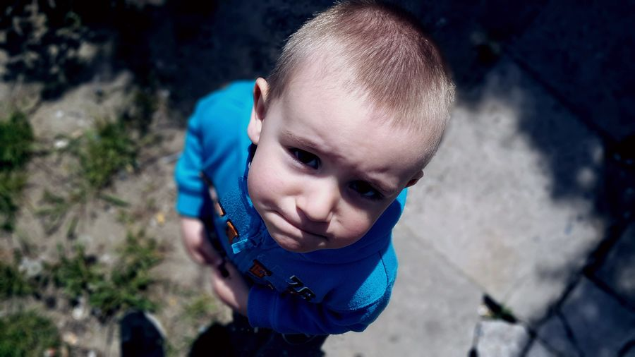 High Angle Portrait Of Boy Standing Outdoors