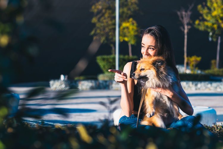 Woman with dog sitting at park