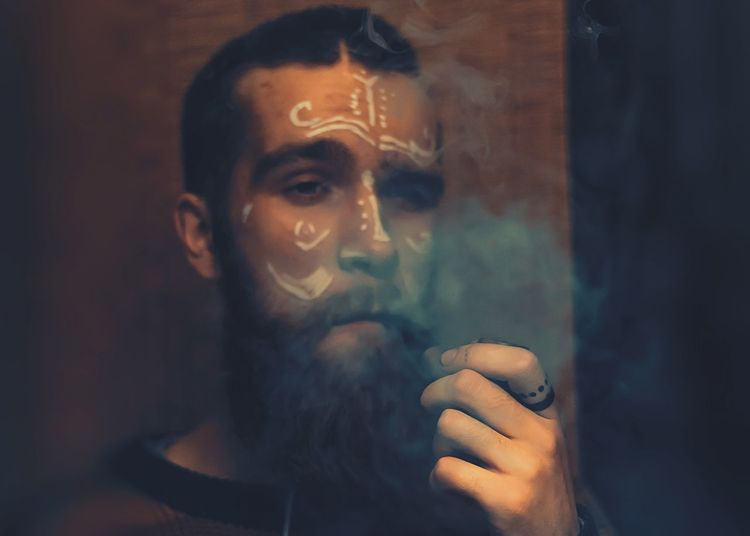 Close-Up Of Man With Face Paint Smoking Pipe