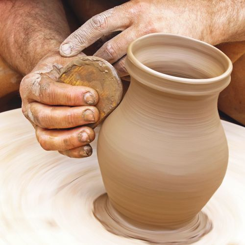Cropped Image Of Hand Making Pot On Wheel