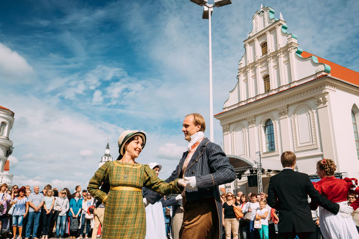 Minsk, Belarus - September 3, 2016: Couple of young people dressed in clothes of the 19th century dancing Polonaise at the celebration of the Day of Minsk city in a historic area Nemiga. Belarus Celebration Church City Couple Dancing Holiday Minsk Music Polonaise Press For Progress Young Century Cloth Culture Dressed Festival History Men Nemiga Pair People Tourism Traditional Women Stories From The City