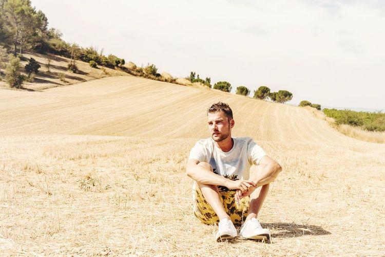 Full Length Of Man Sitting On Dirt Road Against Sky