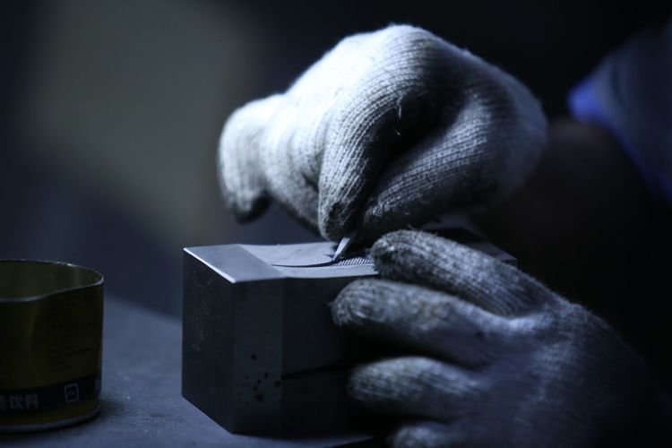 Cropped hands wearing gloves holding box on table