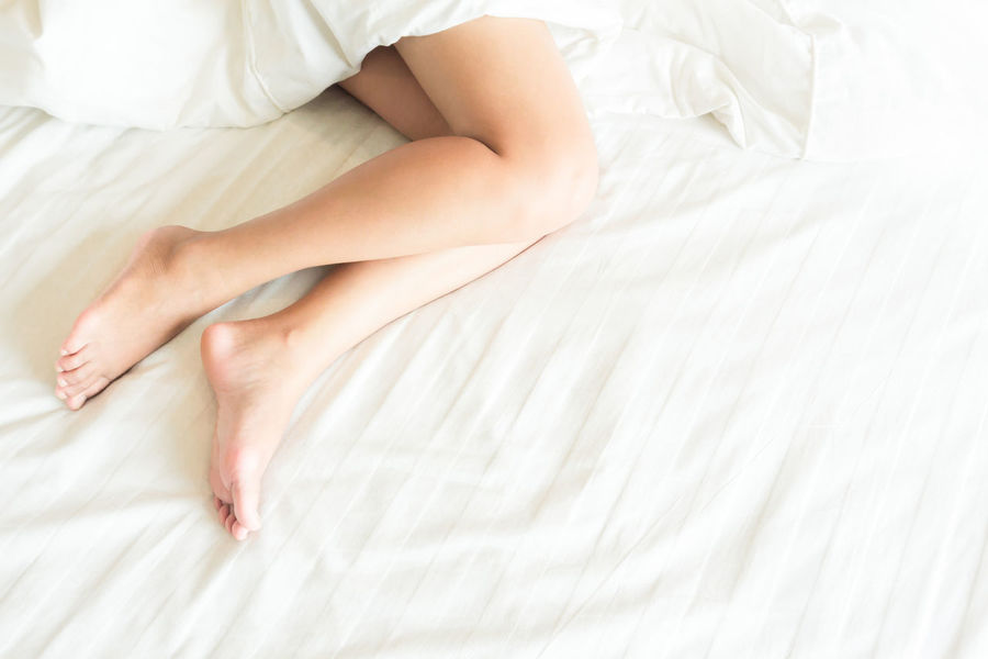 Closeup woman legs on white bed, beauty and skin care concept, selective focus Beautiful Care Females Foot Home Leg Attraction Background Barefoot Barefooted Beauty Bed Bedroom Cultivation Day Depilation Health Low Section Lying Down People Real People Relax Relaxation Sexywomen Top View