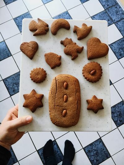 Low section of person holding cutting board with gingerbread cookies
