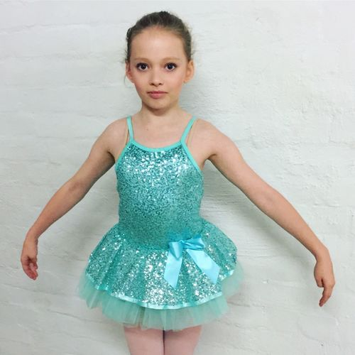 Portrait Of Cute Ballet Dancer Standing Against White Wall