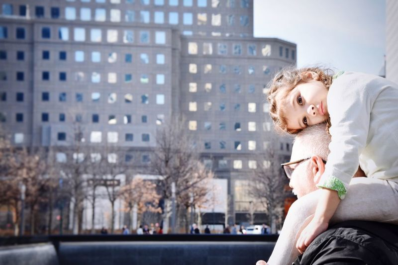 Grandfather Carrying Granddaughter On Shoulders Against Building