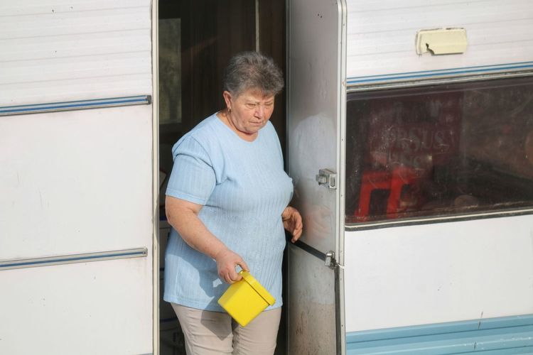 High angle view of woman standing at entrance of camper trailer
