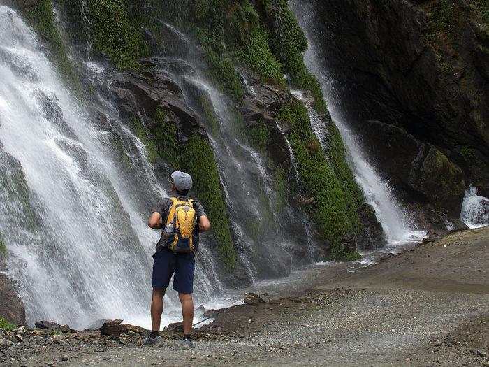 Full length of man standing on rock against waterfall
