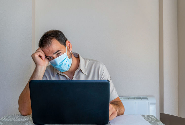 Frustrated man wearing flu mask sitting at office