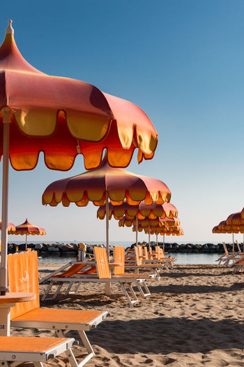Parasols and sunbeds in Torre Pedrera near Rimini in Italy Badeort Strand Urlaub Architecture Baden Beach Beauty In Nature Clear Sky Day In A Row Land Multi Colored Nature No People Orange Color Outdoors Parasol Sand Sea Sky Sonnenliegen Sonnenschirm Sunlight Torre Pedrera Water