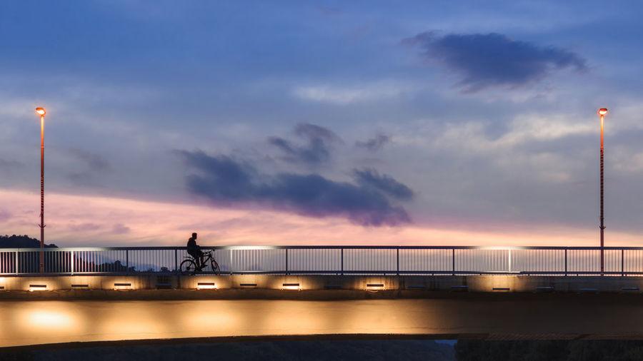 Silhouette bridge over sea against sky at sunset