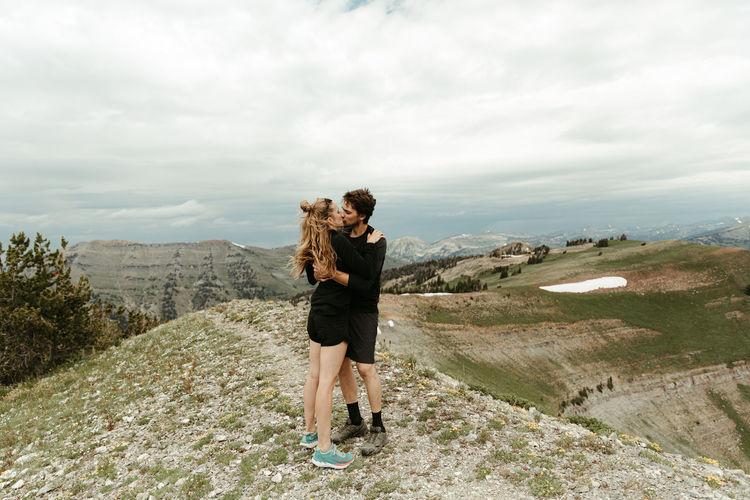 Full length of friends standing on mountain against sky