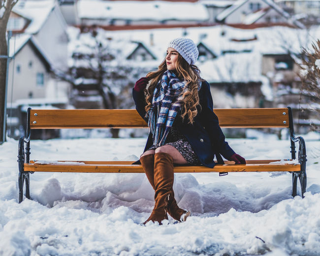 Woman sitting on bench in snow