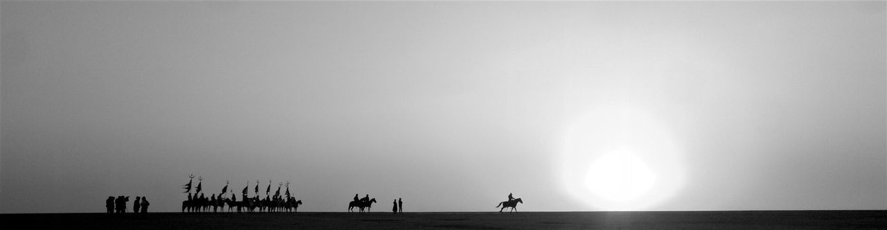 Silhouette Of Army With Horses On Field Against Sky