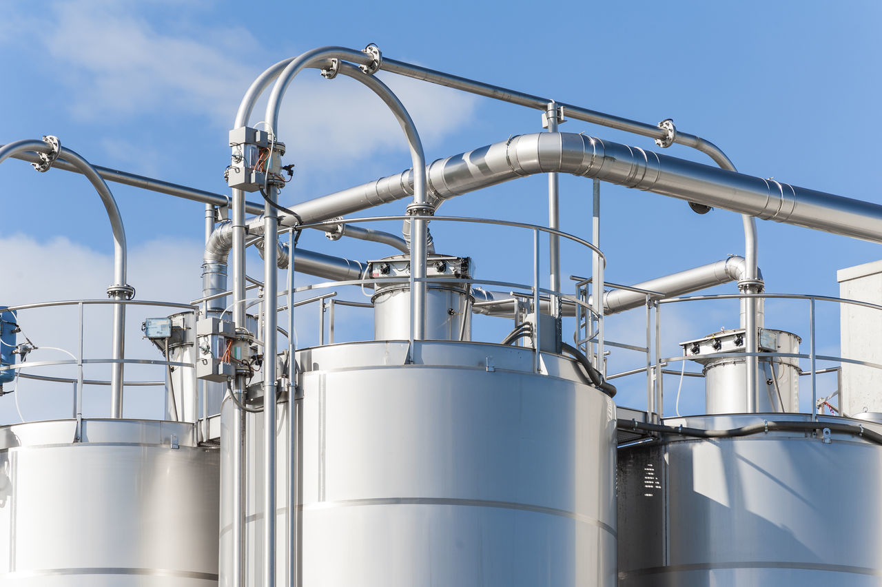 Low Angle View Of Storage Tanks Against Sky During Sunny Day