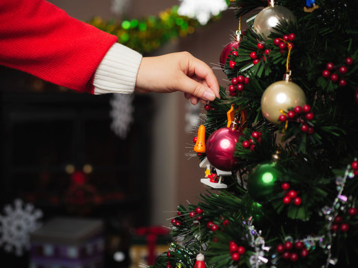 Cropped Image Of Hand Decorating Christmas Tree
