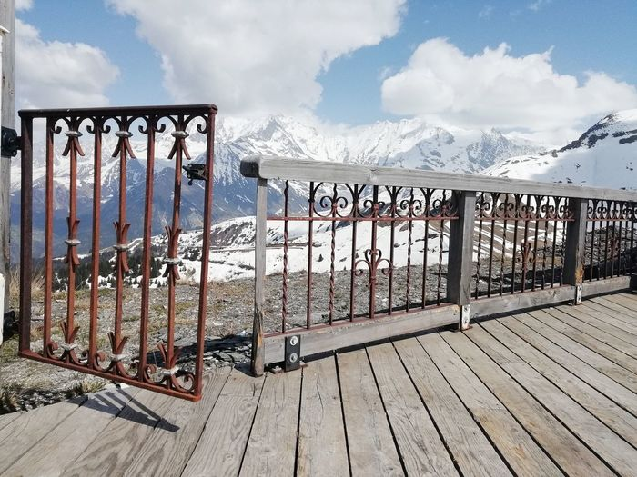 Metal fence on snow covered mountains against sky