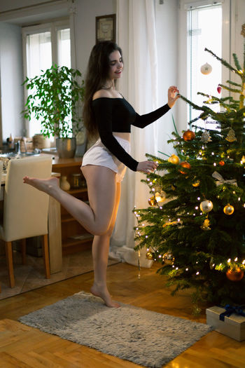 Full length of woman standing by tree at home