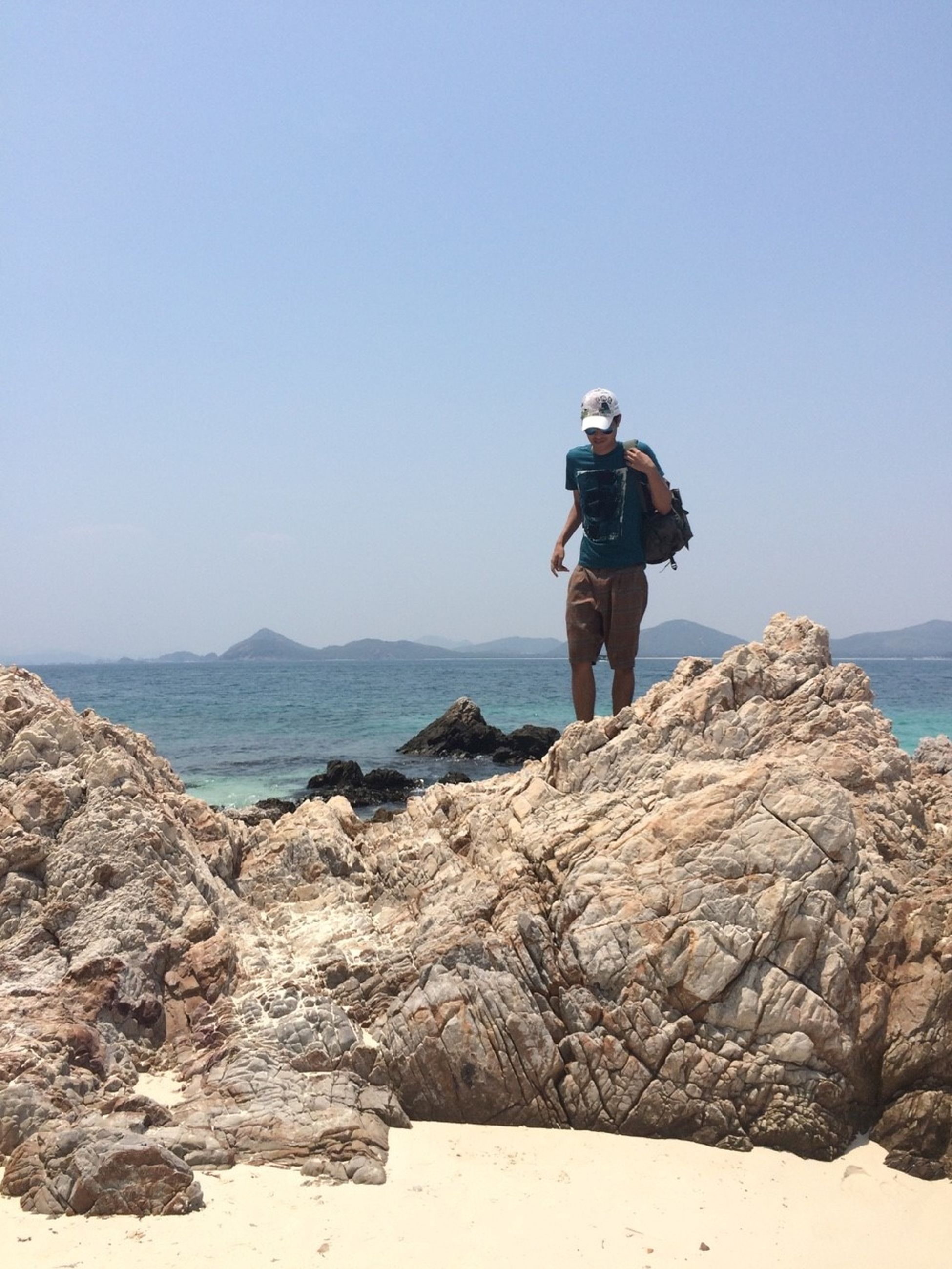 full length, lifestyles, clear sky, leisure activity, sea, rock - object, copy space, casual clothing, standing, water, rear view, nature, tranquility, beach, rock formation, horizon over water, scenics, beauty in nature