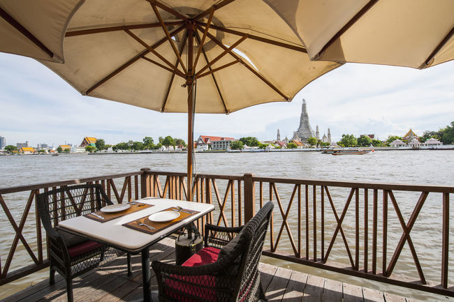 Table at the waterfront Absence Bangkok Chair City Life Cloud Day Empty Group Of Objects Patio Place Setting Railing Relaxation Sky Sunshade Table Table For Two Thailand Tranquil Scene Tranquility Vacations Wat Arun (Temple Of Dawn) Water Waterfront