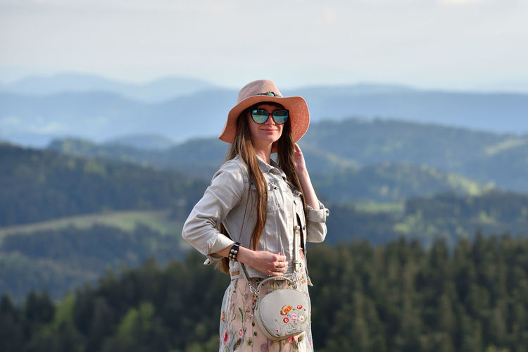 Woman wearing sunglasses standing against mountain