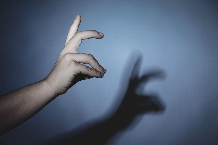 Cropped hand gesturing with shadow on wall