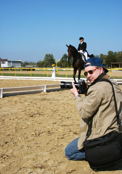 Kneeling Professional Press Photographer Who Turned His Head Our Way, Shoots Outdoor Equestrian Dressage Style Classic English Riding Sports Competition - Horsewoman Jokey on a Dark Brown Purebred Striding Horse in the Background Dressage Horsewoman Photojournalist Press Professional Work Skill  Back Turned Competitive Dressage Correspondent English Riding Equestrian Ground Horse Competitions Horse Gait Horse Rink Horse Show Horse Tack Horse Viewing Horseback Riding Jokey Kneeling Photographer Lens Racing Field Turned Head Vertical Press For Progress EyeEmNewHere