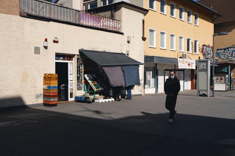 Man walking on street by buildings in city