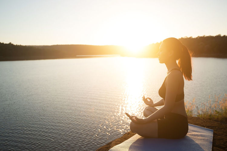 Side view of woman meditating while sitting on rock at lakeshore during sunset