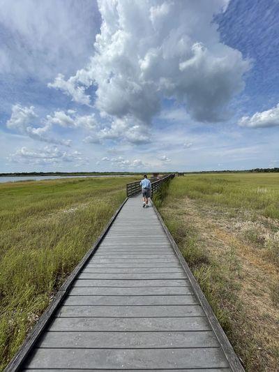 Boardwalk amidst field against sky