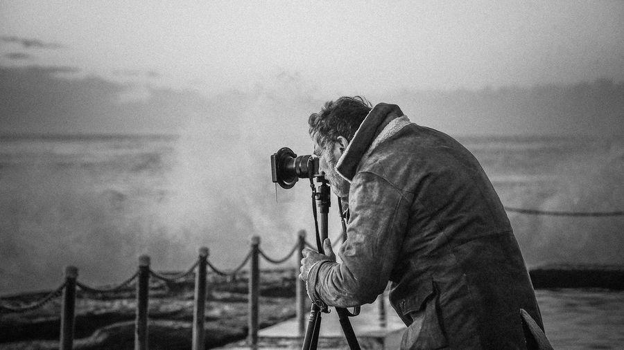 Man Photographing Sea Waves Through Tripod Camera From Promenade
