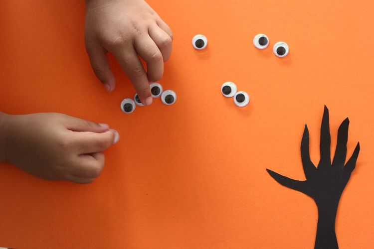 Close-up of hands playing with doodle eyes on orange background