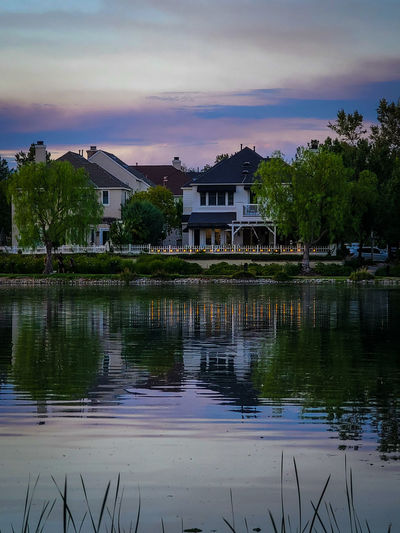 Houses by lake and buildings against sky at sunset