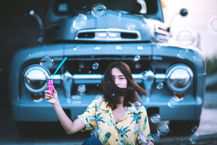 Every summer has its own story. Young Woman With Bubble Wand and Car background. Bubbles Cars Celebration Ford F100 Happiness Happy Holiday Light Lights Love Beautiful Woman Bokeh Bubble Car Hairstyle Lifestyles Light And Shadow Light In The Darkness Mode Of Transportation Portrait Transportation Vintage Wind Women Young Women