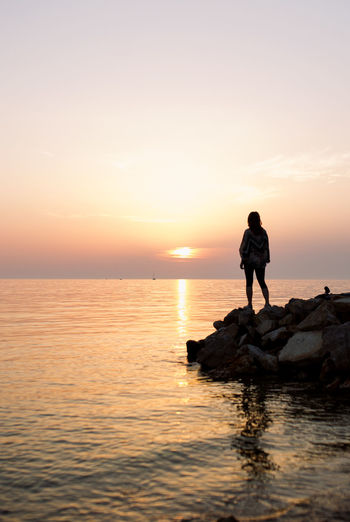 Man standing on rock in sea against sky during sunset