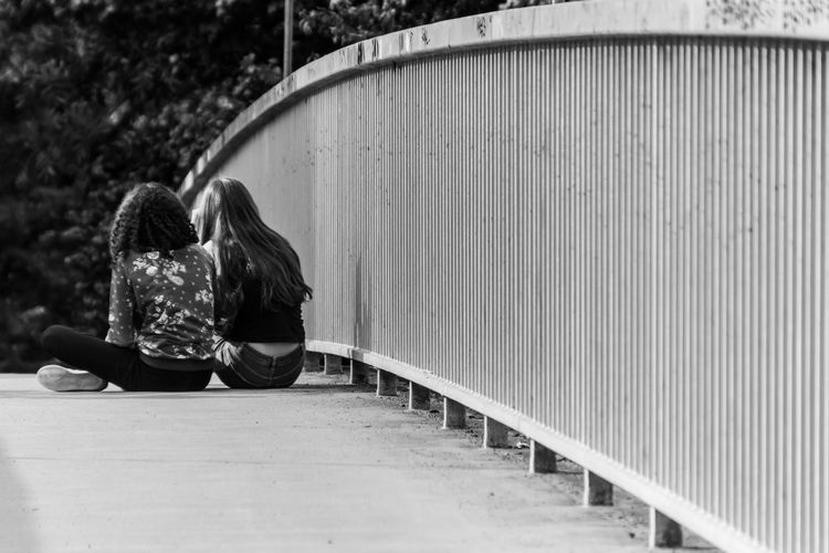 Bridge Casual Clothing Day Focus On Foreground Freundinnen Friends Friendship Fußgängerbrücke Geländer Lifestyles Outdoors Pedestrian Pedestrian Walkway Person Railing Rear View Relaxation Sitting Street Photography Summer Togetherness